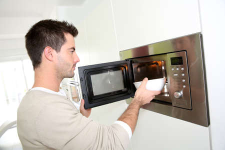 microwave oven: Man heating food in microwave