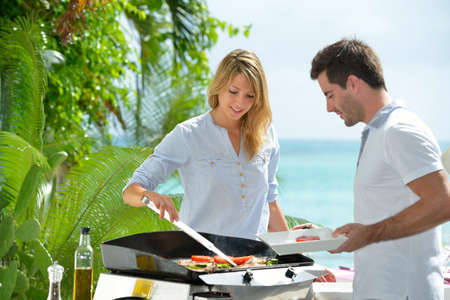 Cheerful couple preparing grilled food on barbecue photo