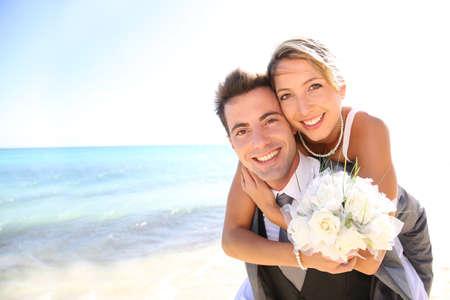 outdoor wedding: Groom giving piggyback ride to his bride Stock Photo