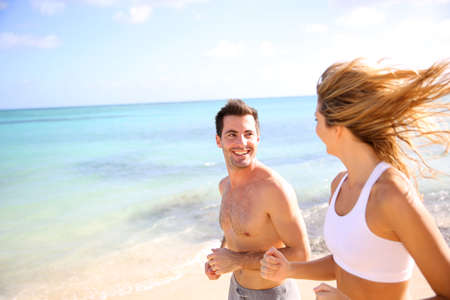couple exercising: Cheerful couple training on the beach