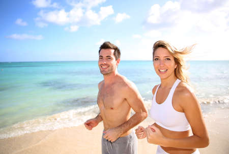 Cheerful couple training on the beach photo