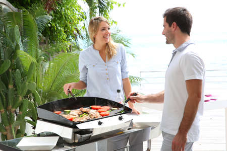 vacation home: Cheerful couple preparing grilled food on barbecue Stock Photo