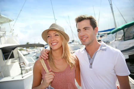 recreational vehicle: Couple of tourists walking by harbour Stock Photo