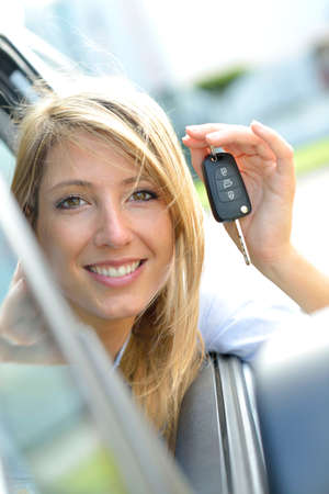 Cheerful young woman showing car key photo