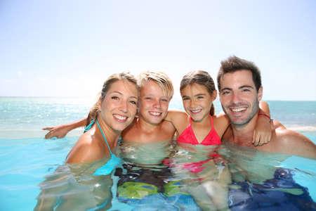 pool fun: Happy family enjoying bath time in infinity pool