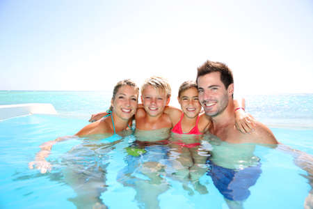 Happy family enjoying bath time in infinity pool photo