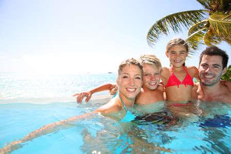 Happy family enjoying bath time in infinity pool photo