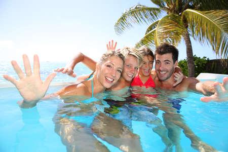 adultos: Familia feliz disfrutando de la hora del ba�o en la piscina de borde infinito
