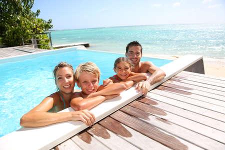 child in bikini: Happy family enjoying bath time in infinity pool
