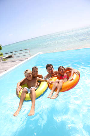 swimmingpool: Parents having fun with kids in swimming-pool Stock Photo