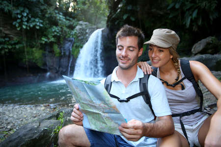 Hikers looking at map by waterfall photo
