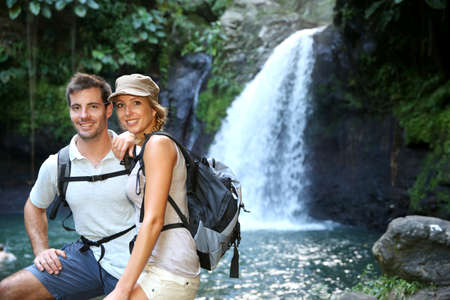 adventurers: Trekkers reaching waterfall in natural landscape