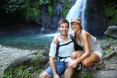 Trekkers reaching waterfall in natural landscape photo
