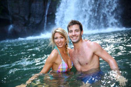 adventurers: Cheerful couple enjoying river bath by waterfall Stock Photo