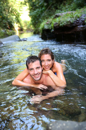 adventurers: Cheerful couple bathing in river waters Stock Photo