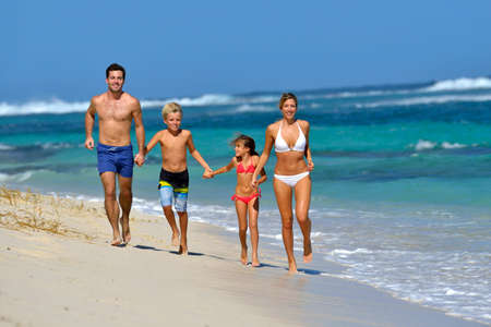 Family running on a sandy beach photo