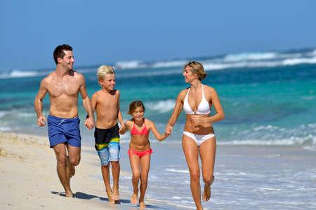 child bikini: Family running on a sandy beach