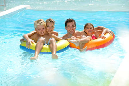 infinity pool: Parents having fun with kids in swimming-pool Stock Photo