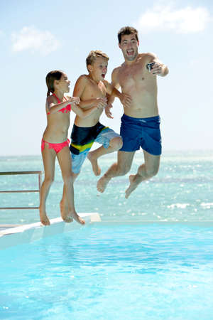 Man with kids jumping in swimming pool water photo