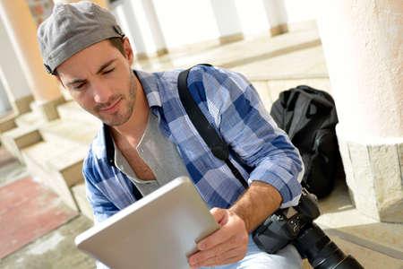 aventurero: Aventurero mirando a tiros de la foto en la tableta Foto de archivo