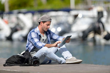 globetrotter: Adventurer looking at photo shots on tablet