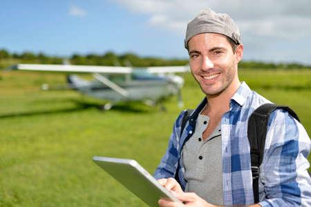 aerodrome: Adventurer using digital tablet in aerodrome