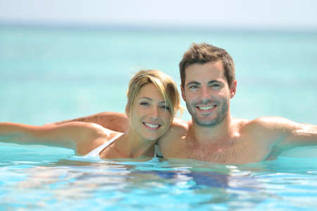 Couple swimming in infinity pool photo