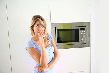 Portrait of woman by microwave oven Stock Photo - 24761914