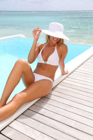 chic woman: Beautiful chic woman sitting by pool in white bikini
