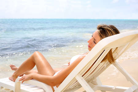 Woman relaxing in long chair by the beach photo