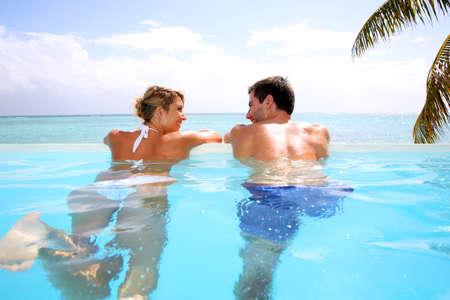 infinity pool: Cheerful couple swimming in infinity pool Stock Photo