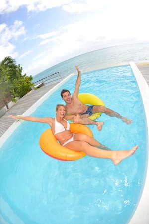 Cheerful couple having fun in swimming-pool photo
