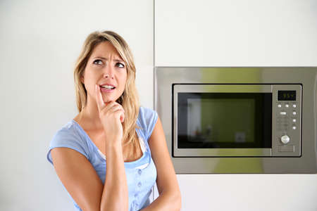 Portrait of woman by microwave oven photo