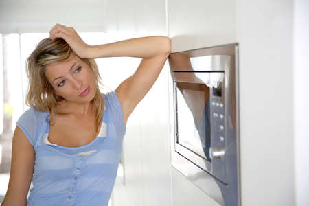 Portrait of woman by microwave oven Stock Photo - 24761853