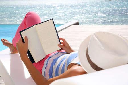 mujer leyendo libro: Libro de lectura de la mujer se relajó en la silla de cubierta Foto de archivo