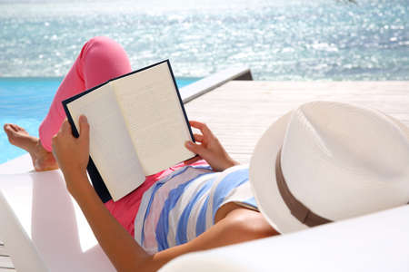 reading book: Woman reading book relaxed in deck chair Stock Photo