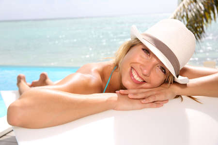 suntanning: Fun girl with hat suntanning by the pool Stock Photo
