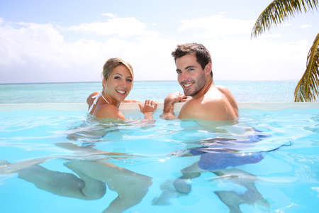 Cheerful couple swimming in infinity pool Stock Photo - 24761843
