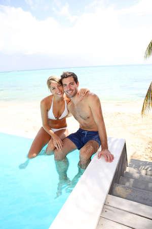 Cheerful couple swimming in infinity pool photo