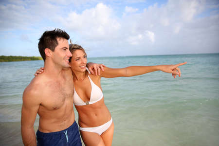 Couple walking by the beach in tropical island photo