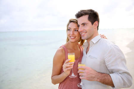 Couple enjoying cocktail on caribbean beach photo