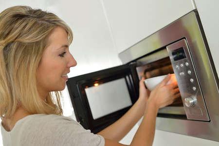 refei��es: Mulher em casa usando forno de microondas