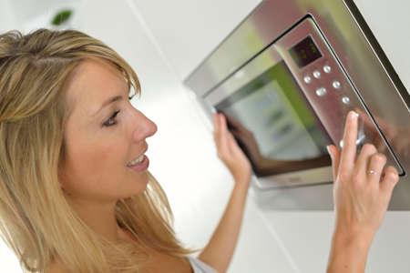 여자가 집에 전자 레인지를 사용하여