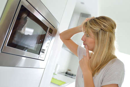 Woman at home using microwave oven photo