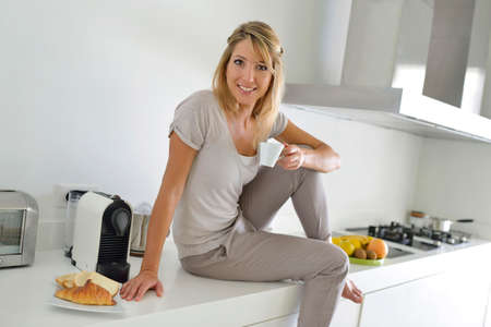 Cheerful young woman having coffee in kitchen photo