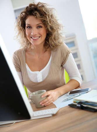 Smiling working girl in front of desktop
