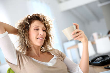 Woman in office relaxing with tea cup photo