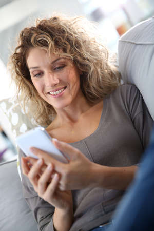 Smiling woman relaxing in sofa with smartphone photo
