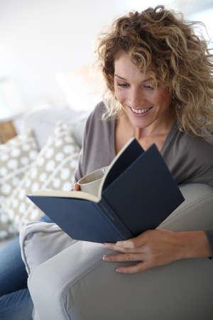 Woman reading book at home in sofa 版權商用圖片