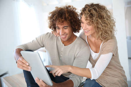 Happy couple at home websurfing on digital tablet